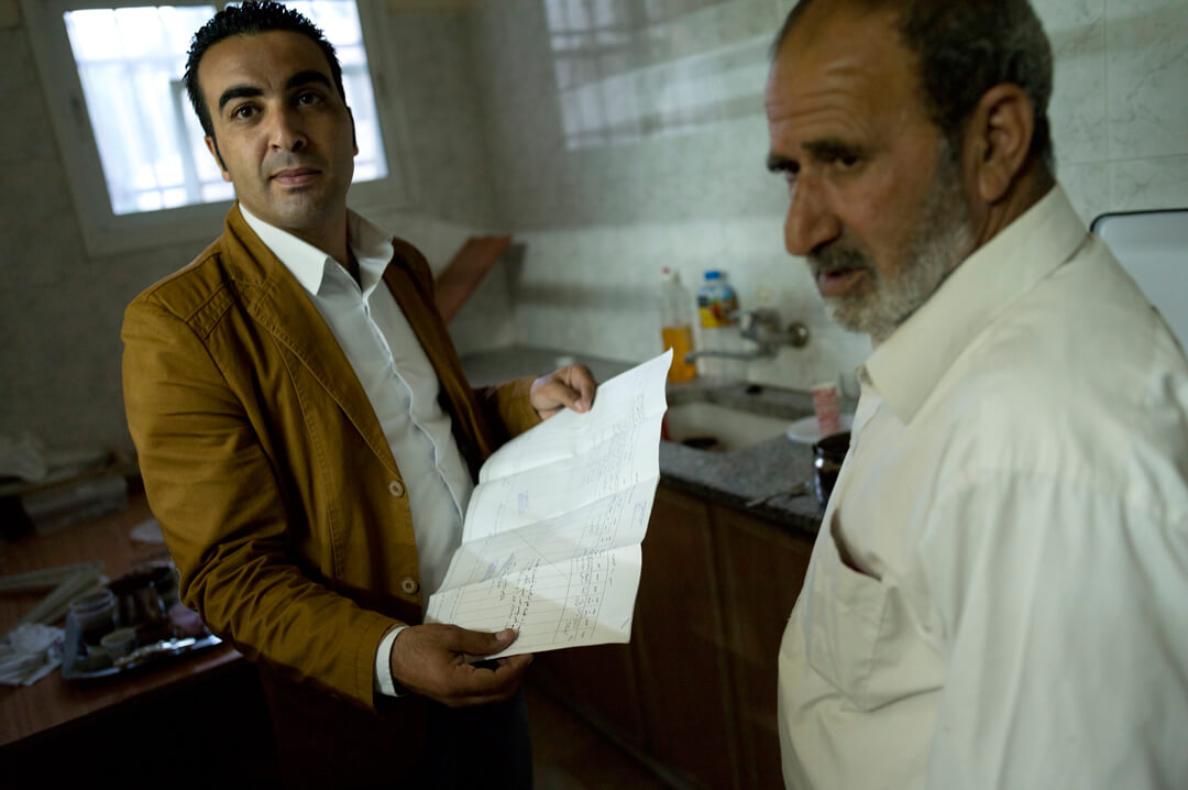 Ahmad Sukkar, the head of the town council in Wadi Fukin, looks over a kushan – a land deed issued during Ottoman times - of a local farmer.  Kushans will be used in court in an attempt to show that the land under threat of seizure is privately owned by Palestinians, and thus unable to be declared state land, and taken by the Israelis. (Photo: Andrew Lichtenstein)