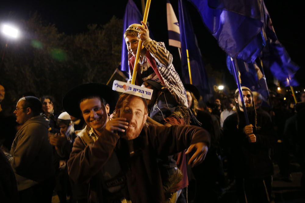 Right-wing Israelis hold a protest in Jerusalem holding masks of shot activist Yehuda Glick (Photo: AFP)