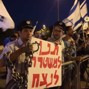 Hebrew University students from the right-wing organization Im Tirtzu wear mock-police uniforms and chains while holding a sign that reads: Let the police win. (Photo: Dan Cohen)