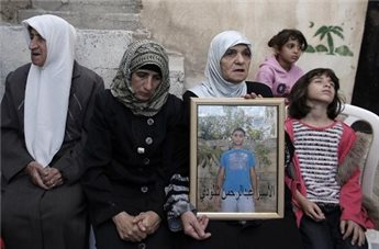 The mother (2L) and family members of Palestinian Rahman al-Shaludi hold his portrait at their family home in East Jerusalem. (Photo: Ahmad Gharabli/AFP) al-Shaludi hold his portrait at their family home in East Jerusalem on Thursday. (Photo: Ahmad Gharabli/AFP)
