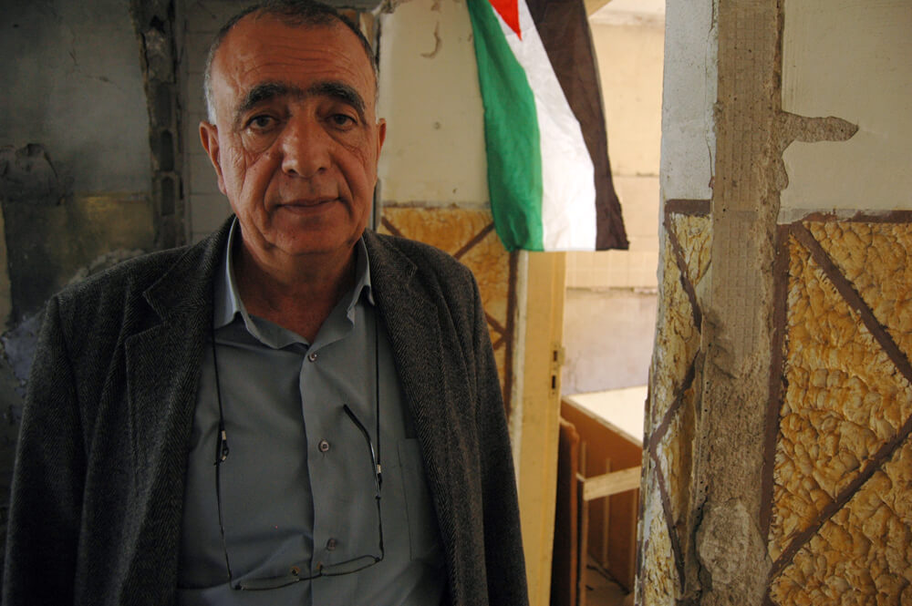 Abdel Karim al-Shaloui stands in the former salon of Abdel Rahman al-Shaludi's apartment, hours after Israeli authorities demolish it by explosion. (Photo: Allison Deger)