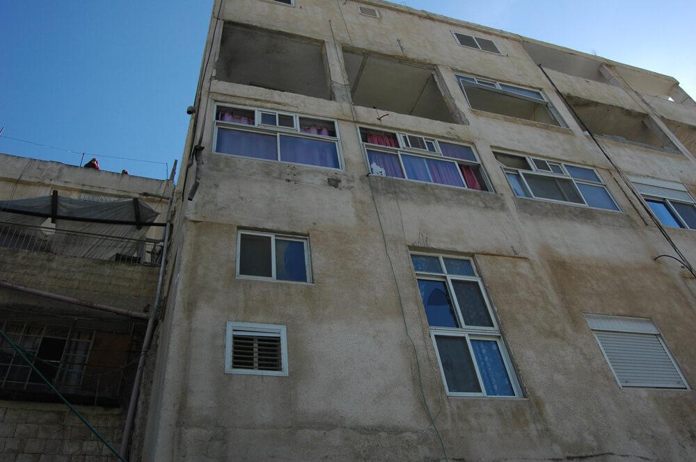 Blown out windows of the apartment of Abdel Rahman al-Shaludi. (Photo: Allison Deger)