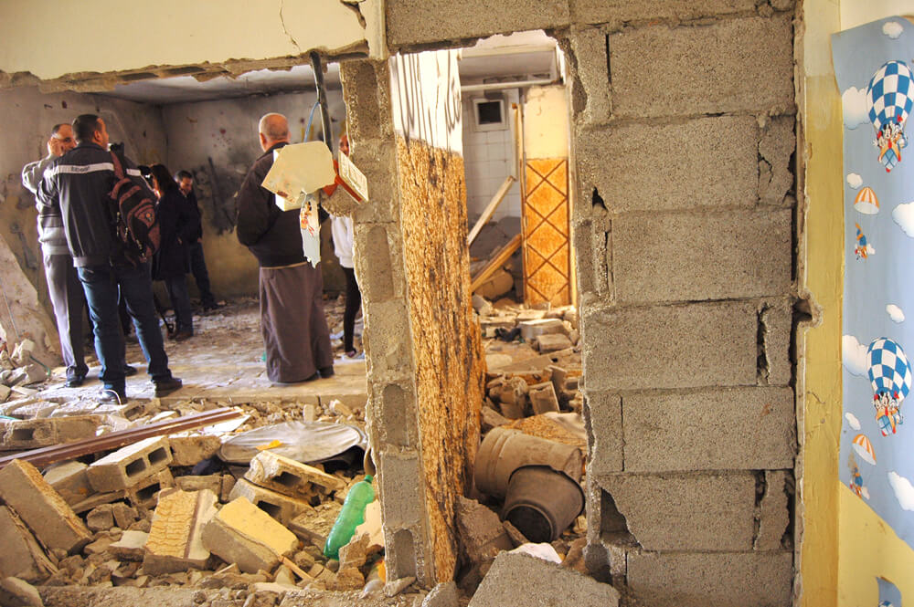 Relatives of Abdel al-Shaludi assess the interior of his home, demolished by explosives. (Photo: Allison Deger)