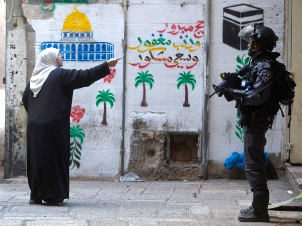 A Palestinian woman shouts at Israeli policemen in the old city of Jerusalem on Thursday after Israeli authorities temporarily closed the al-Aqsa mosque compound, October 31, 2014. (Photo: AFP/Menahem Kahana)