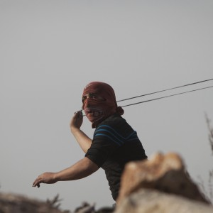 A Palestinian uses a sling shot during clashes with Israeli forces following a protest against Israeli restrictions to Al-Aqsa Mosque in Jerusalem, at the Qalandia checkpoint near the West Bank city of Ramallah, Friday, Nov. 14, 2014. (Photo: AP/Majdi Mohammed)