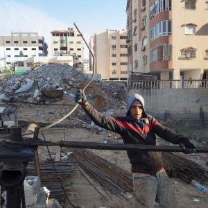 Mohammed Shukri Mohammed Khrewat, 21, works to straighten rebar from the rubble of the Zafer 4 Tower. (Photo: Dan Cohen)