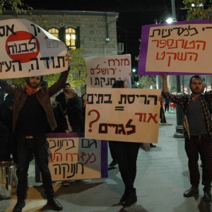 "Israeli activists came out last week to protest Mayor Nir Barkat's ritual Chanukah candle lighting in Jerusalem. (From left to right): ""No building allowed. Yours, the City""; ""House demolitions = Or Lagoyim"" [Jewish phrase for lighting the way to Gentiles]; ""Stop the 'quiet transfer policy'"" (Photo: Sarah Levy)"