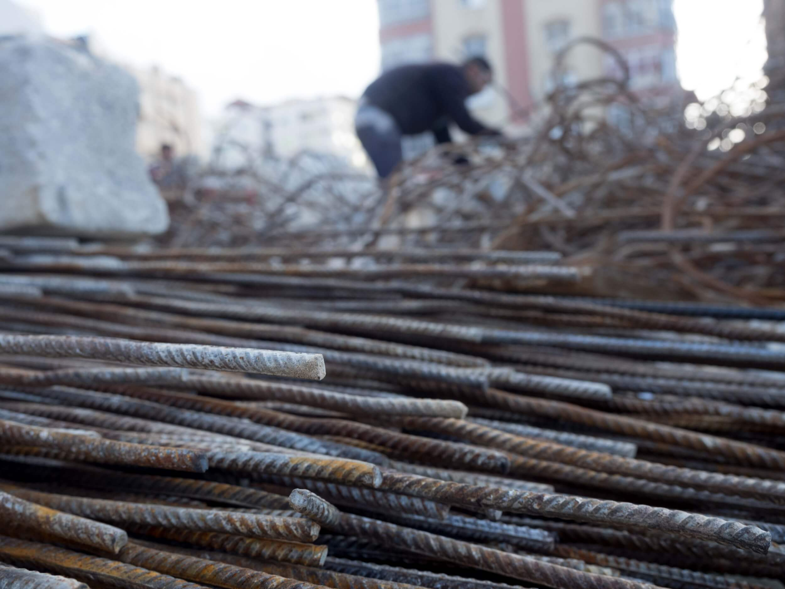 A worker at the Zafer 4 Tower rubble salvages rebar that will be used to rebuild. (Photo: Dan Cohen)