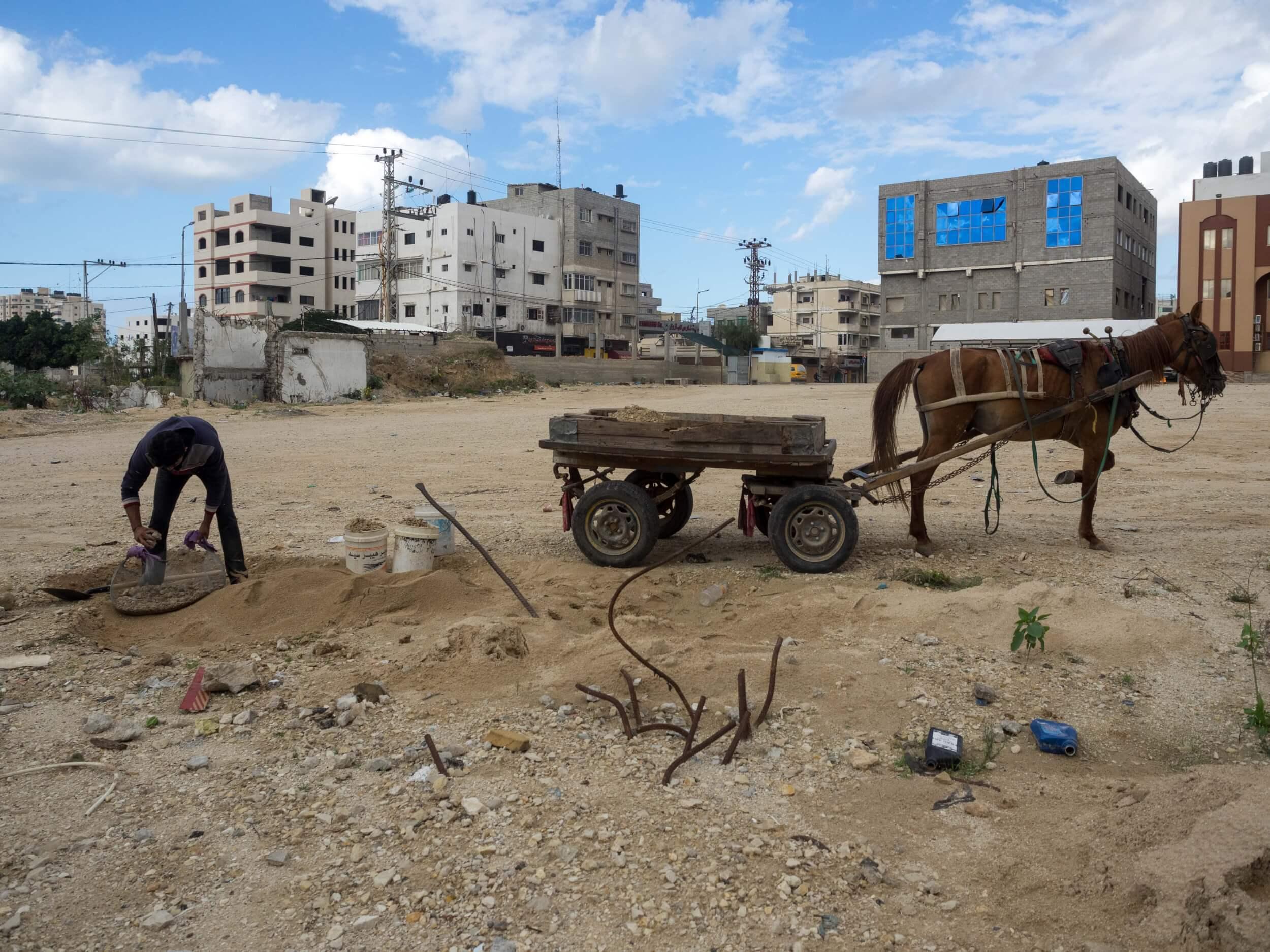 Mohammed Majd Hosni Al-Madhoun, 23, collects rocks in a lot in Gaza City. (Photo: Dan Cohen)