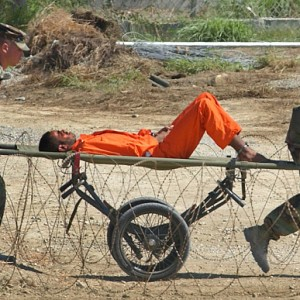 A detainee from Afghanistan is carried on a stretcher before being interrogated by military officials at Camp X-Ray at the U.S. Naval Base in Guantanamo Bay, Cuba in 2002. (Photo: LYNNE SLADKY/AP)