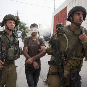 Israeli soldiers arrest a Palestinian man during a search for three missing Israeli teens in the West Bank, June 21, 2014. (AP Photo/Majdi Mohammed)