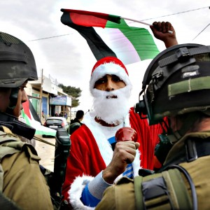 A Palestinian protester dressed as Santa Claus holds a Palestinian flag as he argues with Israeli soldiers during a demonstration against Israeli settlements in the village of Maasara near the West Bank city of Bethlehem. (Photo: Mussa Qawasma/Reuters)