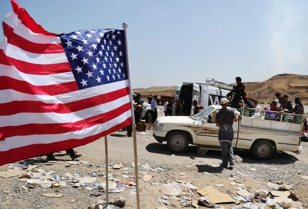 A U.S. flag waves while displaced Iraqis from the Yazidi community cross the Syria-Iraq border on Feeshkhabour bridge over Tigris River at Feeshkhabour border point, northern Iraq. (Photo: Khalid Mohammed/AP)
