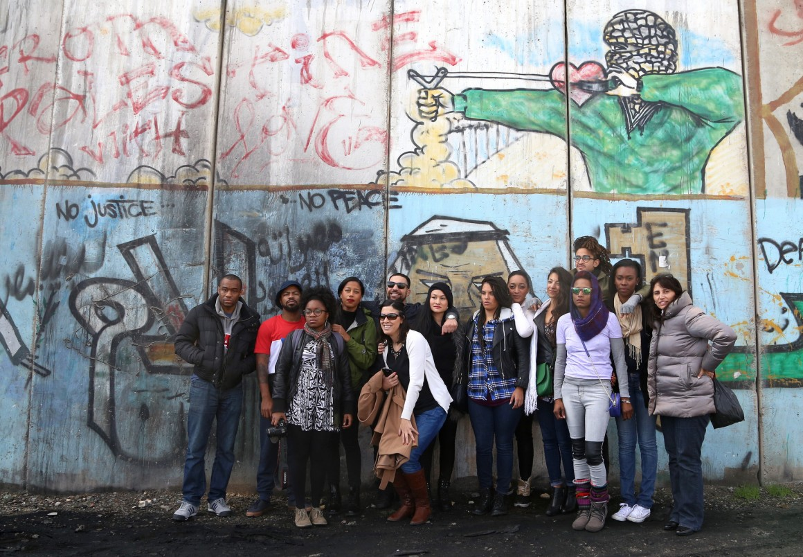 Delegates on the Dream Defenders delegation pose in front of Israel's West Bank wall, near Qalandia checkpoint (Photo: Christopher Hazou, IMEU)