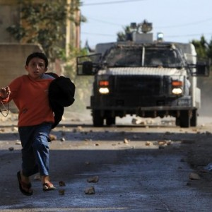 "A Palestinian child runs for cover as an Israeli military vehicle (background) sprays a foul-smelling spray known as ""skunk"" in the village of Kafr Qaddum, near Nablus in the occupied West Bank, on December 5, 2014. (Photo: AFP / Jaafar Ashtiyeh)"