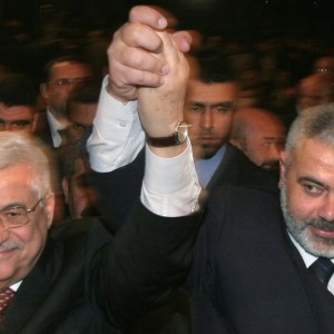 Palestinian Authority President Mahmoud Abbas, left, and Prime Minister Ismail Haniyeh from Hamas, right, raise their linked arms as they move through the crowd at a special session of parliament in Gaza City, March 17, 2007. (Photo: Hatem Moussa/AP/The Times of Israel)