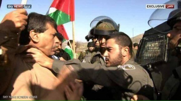 Image of Palestinian Minister Zaid Abu Ein being confronted by Israeli forces,  near Turmusaya, West Bank, Palestine (Image: Sky News via Yousef Munayyer)