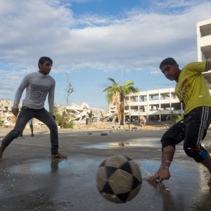 Palestinian boys from Shujaiya play soccer in front of their school that collapsed from Israeli shelling last summer. (Photo: Dan Cohen)