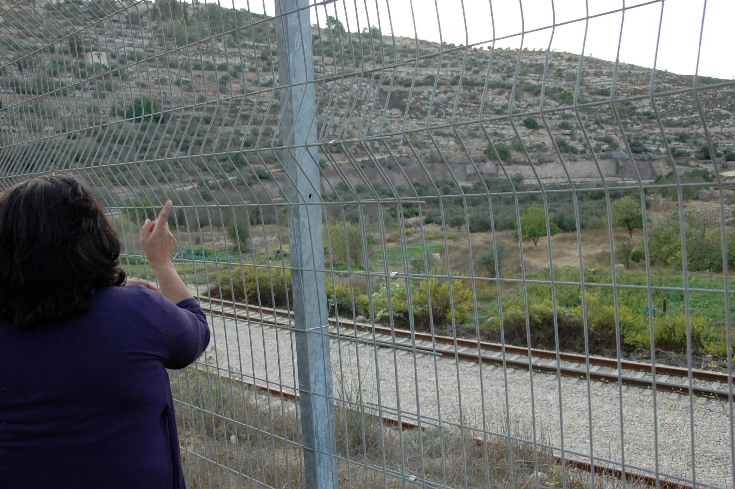 A woman from Battir looks through a fence that currently stands in place of a wall, pointing to her own land on the other side. (Photo: Sarah Levy)
