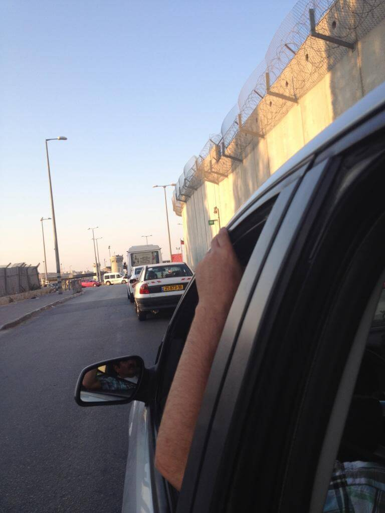 The Wall is seen as my family and I wait in hours-long traffic to be checked at an Israeli checkpoint on our way to Ramallah in Beit Hanina. (Photo: Samah Assad)