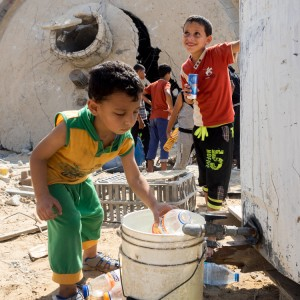 Palestinian children in the Gaza town of Khuza'a fill bottles from a tank in front of the destroyed village reservoir. (Photo: Dan Cohen)