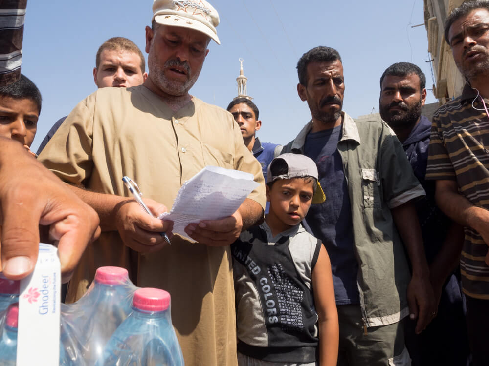A Palestinian man distributes bottled water to families in Khuza'a. (Photo: Dan Cohen)