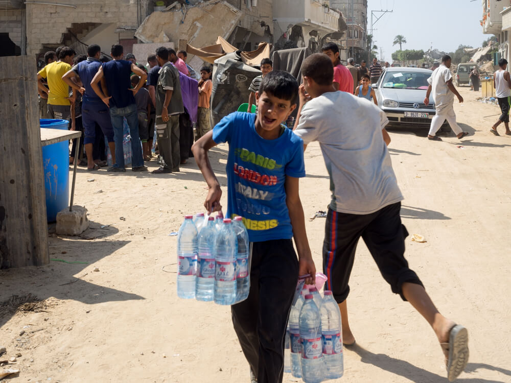 A Palestinian boy carries bottles of water to his home in Khuza'a. (Photo: Dan Cohen)