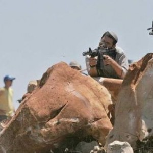 Settlers raise guns at Palestinians near Nablus on August 7, 2009 (Photo: AP)