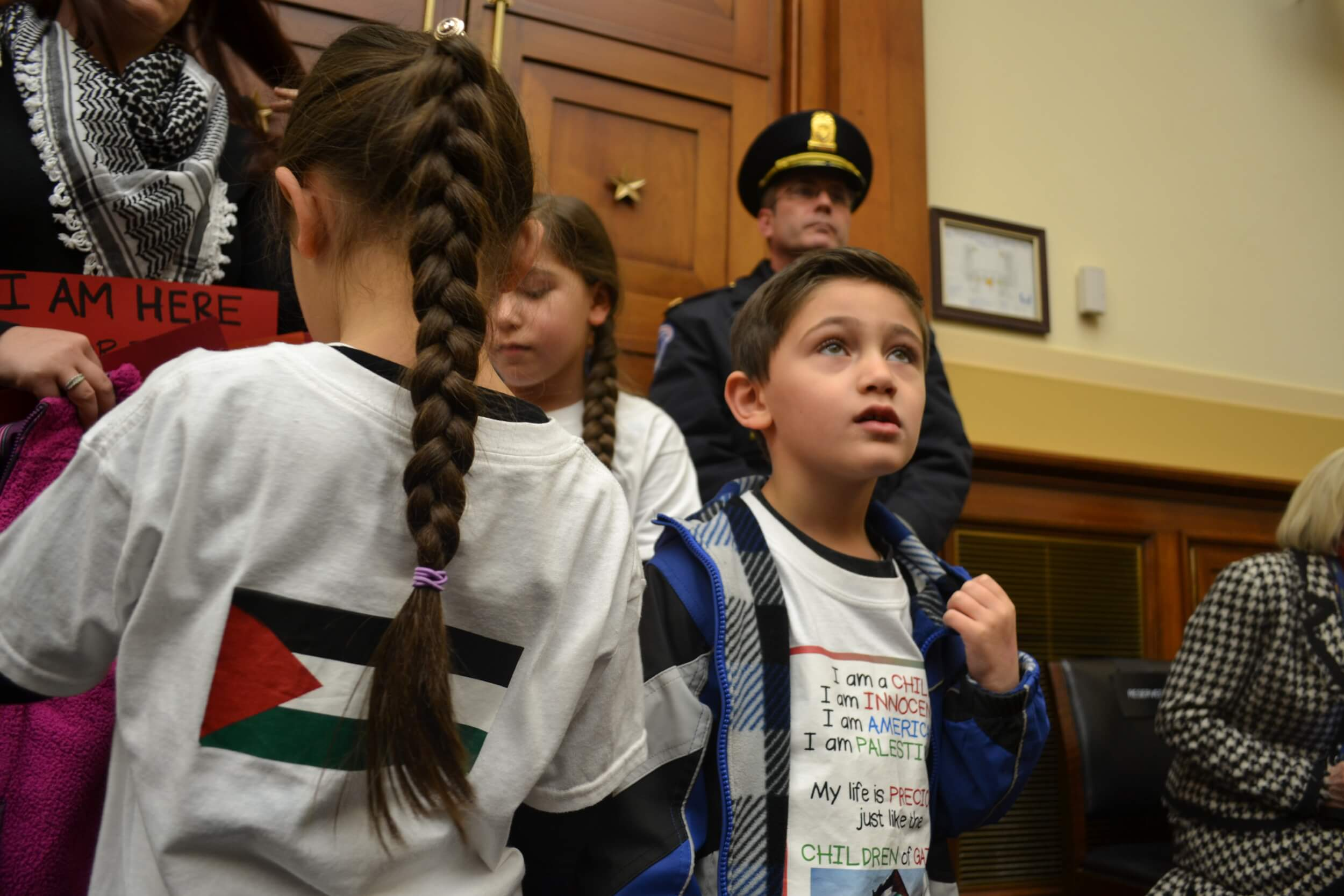 A family arrives late to the hearing, to show support for holding Israel accountable. A Capitol Police officer watches proceedings next to the door. (Photo: Sam Knight)