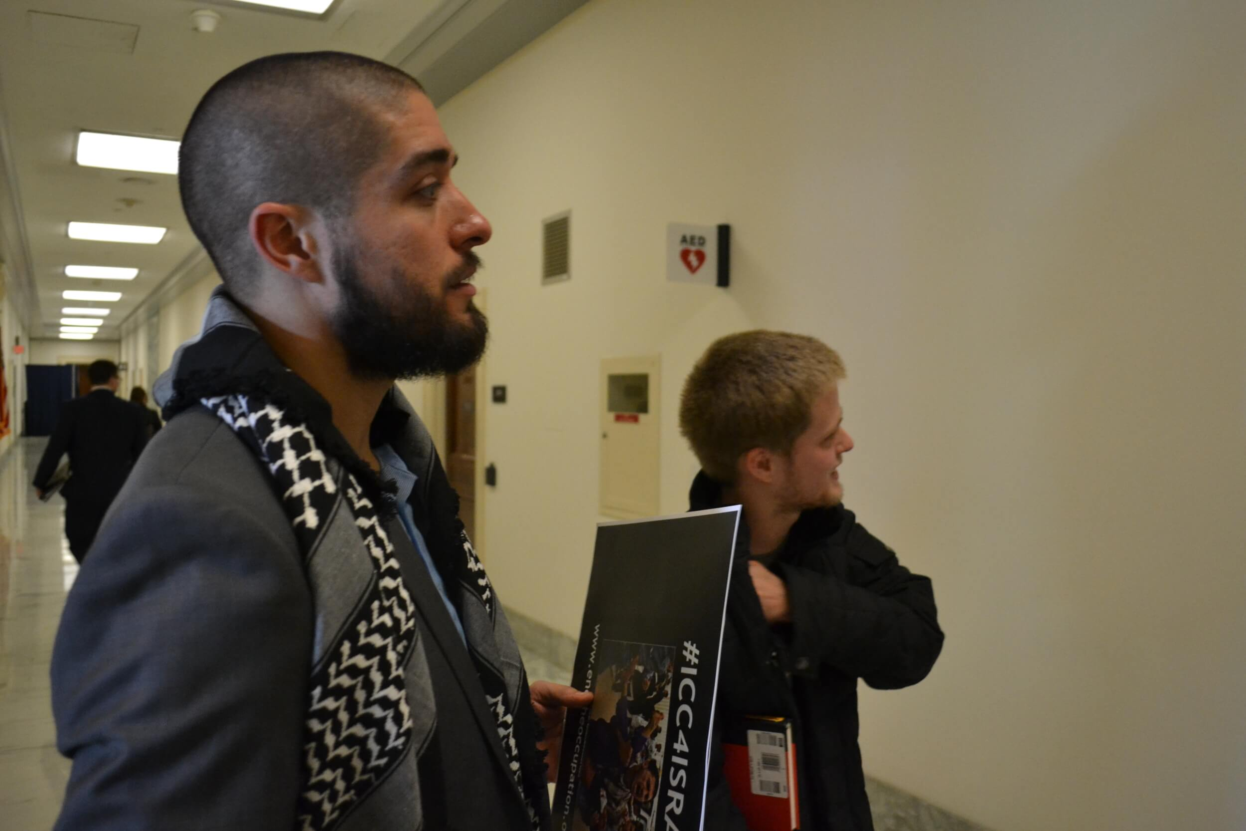 In the hallway outside of the Rayburn hearing room, the man with the kuffiyeh who was promptly asked to leave by Capitol Police after the hearing adjourned. (Photo: Sam Knight)