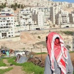 A Palestinian looks at the Israeli settlement Har Homa in the West Bank.