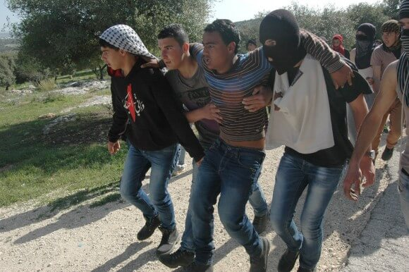 Palestinian youth is carried after being shot in the leg with live fire by the Israeli army in theWest Bank village of Bil'in, February 27, 2015. (Photo: Allison Deger)