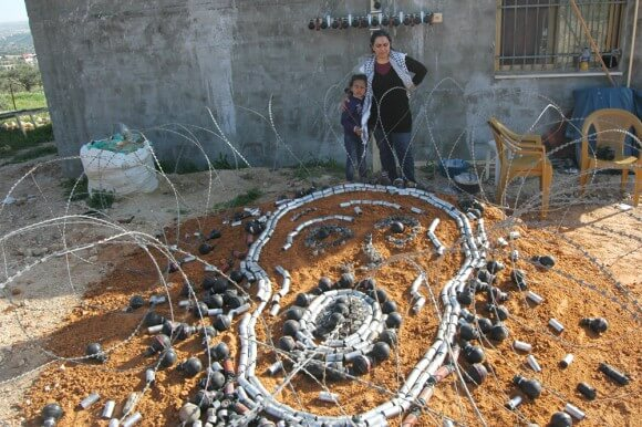 Palestinian artist Rana Bishara stands between two sculptures she produced from spent tear gas canisters and pieces of Israel's separation barrier, February 27, 2015. (Photo: Allison Deger)