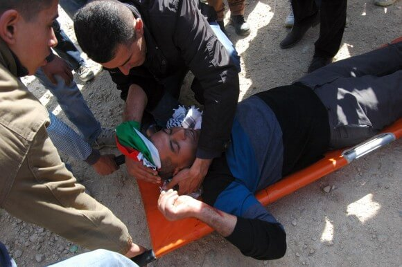 Palestinian injured by Israeli army is transported to n ambulance in the West Bank village of Bil'in. (Photo: Allison Deger)