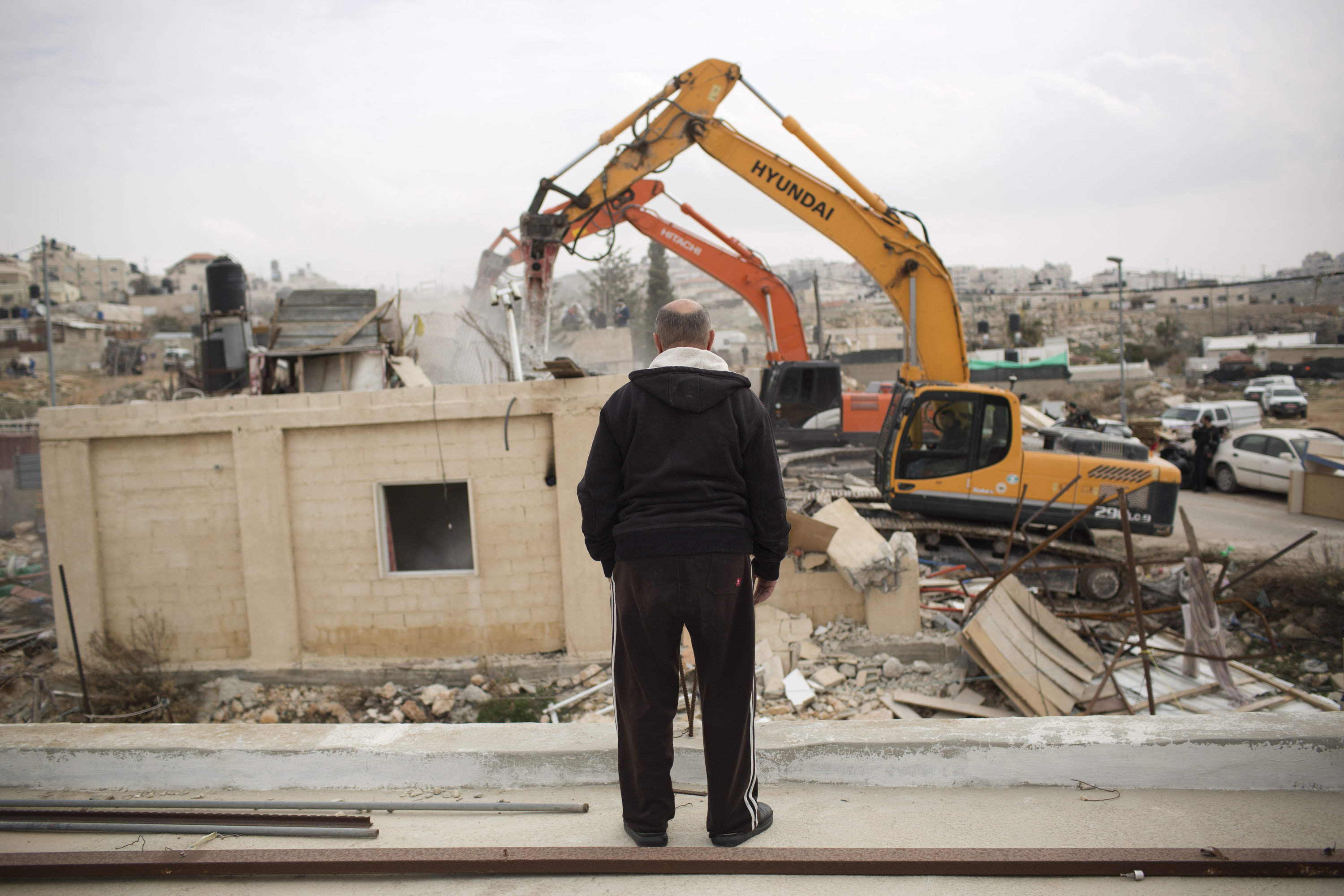 A member of the Adgluni family watching his house being demolished by Israeli authorities in Beit Hanina, East Jerusalem on January 27, 2014. The Israeli authorities claimed the house was built on lands that do not belong to the family. (Photo: Activestills)
