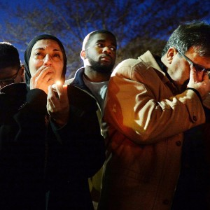 Namee Barakat, right, wipes away tears as he and his wife, Layla, left, watch photos projected on a screen during a vigil for his son, daughter-in-law and her sister, who were killed at a condominium near UNC-Chapel Hill, Wednesday, Feb. 11, 2015. (AP Photo/The News & Observer, Chuck Liddy)