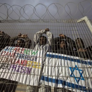 African refugees behind a barbed-wire fence in Israel's Holot detention center in the Negev desert (Photo: Reuters)
