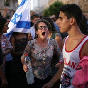 An Israeli yells at a Palestinian at a Jerusalem demonstration. (Photo:  Ilan Assayag/Haaretz)