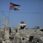 In this Wednesday, Oct. 1, 2014 photo, a Palestinian flag waves as a man walks over the rubble of houses that were destroyed in in Khuzaa, southern Gaza Strip. (AP Photo/Khalil Hamra)