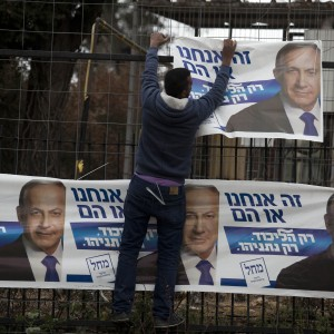 An Israeli worker hangs posters of Israeli Prime Minister and leader of the Likud party Benjamin Netanyahu under the slogan 'It's us or them', in Jerusalem, Israel, 08 February 2015. (Photo: EPA/ABIR SULTAN)