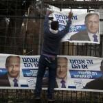 An Israeli worker hangs posters of Israeli Prime Minister and leader of the Likud party Benjamin Netanyahu under the slogan 'It's us or them', in Jerusalem, Israel, 08 February 2015. (Photo: EPA/ABIR SULTAN)