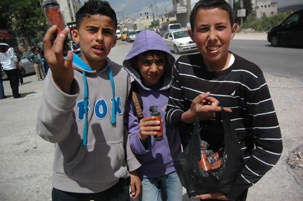 Palestinian children hold up spent tear gas canisters after a Land Day demonstration in the West Bank village of Huwara, south of Nablus, March 30, 2015. (Photo: Allison Deger)