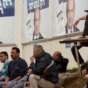 Palestinian workers wait for transportation to go back to the West Bank, next to election campaign billboards of Israel's Prime Minister Benjamin Netanyahu, Likud party leader, in Bnei Brak, Israel. (Photo: Oded Balilty/AP)