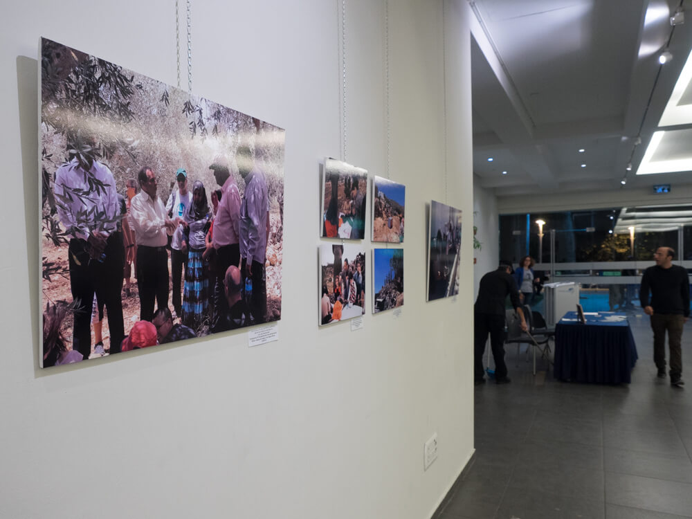 Attendees walk by images from the Occupied West Bank on display. (Photo: Dan Cohen)