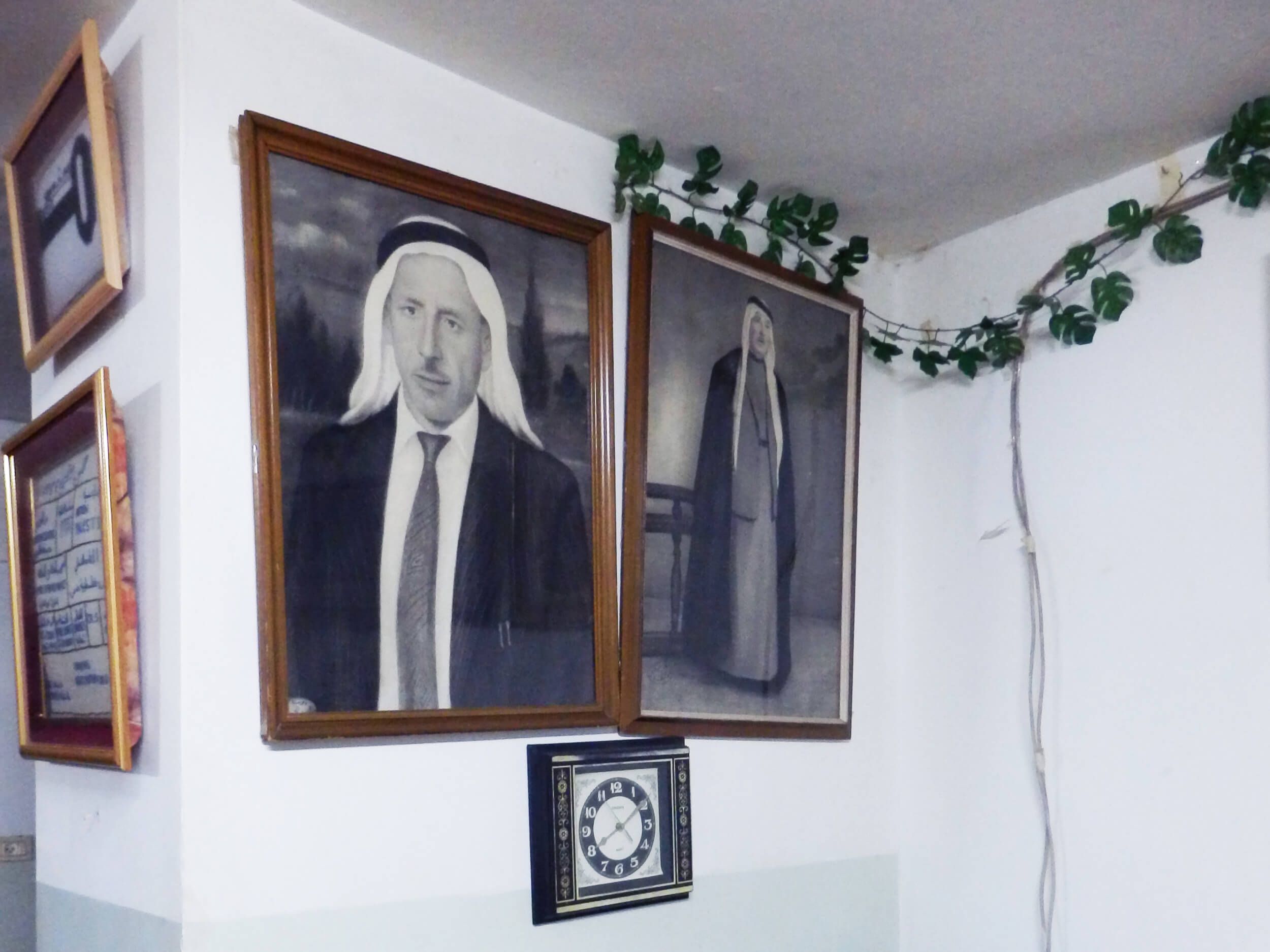 Pictures of the al-'Aza family hang inside Echlas' home in the camp. (Photo: Jacob Burns)