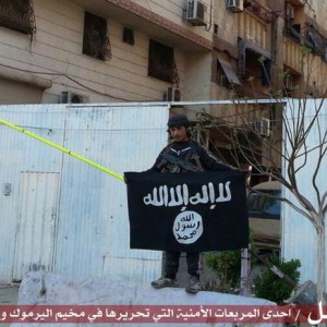 ISIS fighter holds flag inside of Yarmouk refugee camp, Syria. (Photo: Hamshaq/International Business Times)