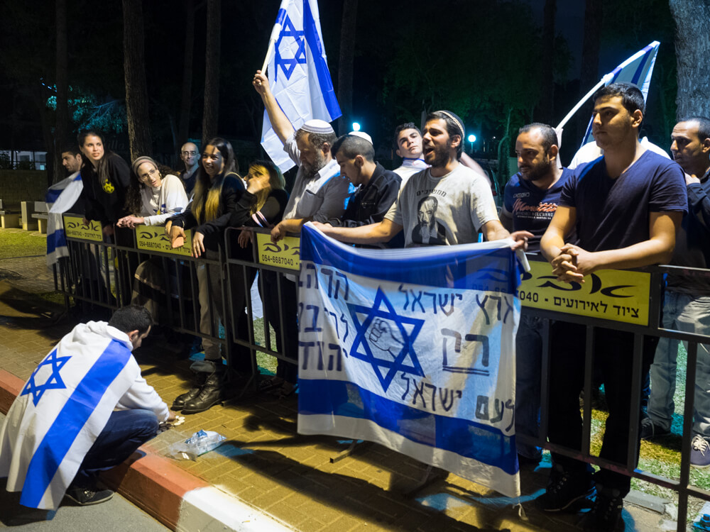 """Lehava fouder Benzi Gopstein led the demonstration. The flag reads """"The State of Israel for only the Israeli people"""" and """"Temple Mount - for Jewish sovereignty."""" (Photo: Dan Cohen)"""