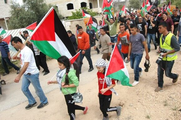 Protesters in Bil'in, the West Bank, mark Palestinian Prisoners Day and the anniversary of the killing of Bassem Abu Rahme, Friday April 17, 2015. (Photo: Allison Deger)