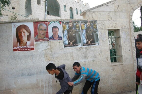 Palestinian children play in front of posters showing the image of Bassem Abu Rahme and imprisoned Palestinians in Bil'in, the West Bank. Friday April 17, 2015. (Photo: Allison Deger)