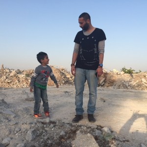 Tamer Nafar, from the rap group DAM, shows solidarity with his son standing on the ruins of one of the houses of the unrecognized Palestinian village of Dahmash, located between the cities of Lod and Ramle in Israel. (Photo provided by Udi Aloni)